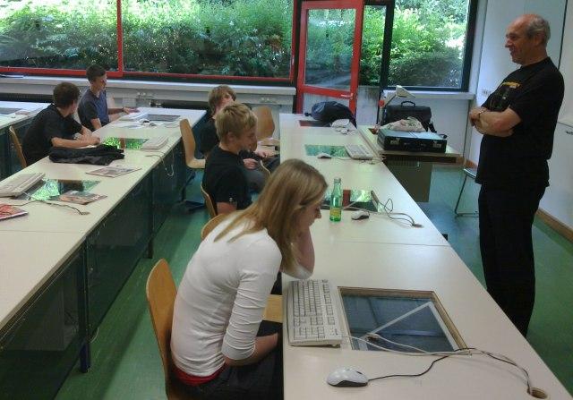 Helmuth Peer unterrichtet vor selbst entworfenen Computertischen